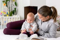 Young mother, reading a book to her baby boy, showing him pictur Stock Image