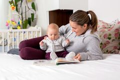 Young mother, reading a book to her baby boy, showing him pictur Royalty Free Stock Photo