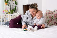 Young mother, reading a book to her baby boy, showing him pictur Stock Photo