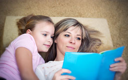 Young mother is reading a book to her daughter. Young mother is reading a book to her cute daughter Royalty Free Stock Image