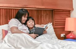 Young mother reading a book to her daughter. Family reading bedtime. Young mother reading a book to her daughter. Happy time in bedroom Stock Photography