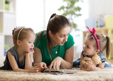 Young mother reading a book to her kids daughters. Children and mom lying on rug in sunny living room. stock photos