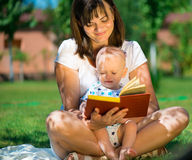 Young mother reading book to her little son Royalty Free Stock Image