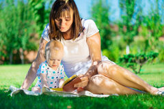 Young mother reading book to her little son Stock Photography