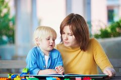 Young mother reading book to her son royalty free stock image