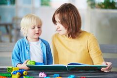 Young mother reading book to her son Royalty Free Stock Photo