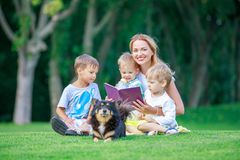 Young mother reading book to her two small sons. Young mother reading book to her small sons while sitting on grass in park. Children and mother enjoying Stock Image