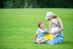 Young mother reading book to her two small sons. While sitting on grass in park. Children and mother enjoying beautiful summer day stock images