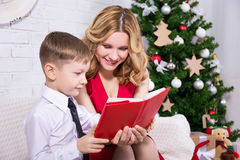 Young mother reading book to his son in front of Christmas tree Stock Image