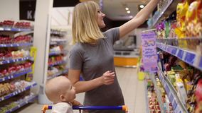 Young mother is reading product contents on the package of cookies and smiling while her little baby is sitting in a stock footage