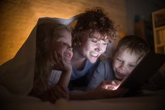 Young Mother Reading Stories with Two Kids. Portrait of happy young mother with two children reading stories in bed, hiding under blanket and using tablet Stock Photos