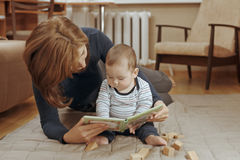 Young mother reading a story to her infant boy Stock Photo