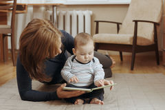 Young mother reading a story to her infant boy Royalty Free Stock Image