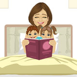 Young mother reading tale story to her children sitting together on bed Stock Image
