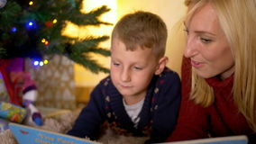 Young mother reading tale to kid under new year tree stock video footage