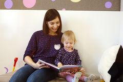 A young mother reads a children`s book for a child. The education of children at home Stock Image