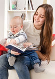 Young mother reads to the child the book Royalty Free Stock Photos