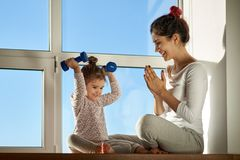 A young mother rejoices at the success of her daughter in sports exercises. Young sports family, promotion of healthy lifestyle royalty free stock photos