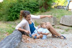 Young mother relaxing outside with her baby son. On the ground pointing to something in front of her with the alert toddler royalty free stock image