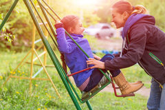 Young Mother Riding Little Daughter on Seesaw in Spring Park Stock Photo
