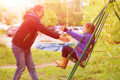 Young Mother Riding Little Daughter on Seesaw in Spring Park Stock Image