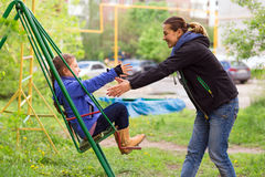 Young Mother Riding Little Daughter on Seesaw in Spring Park. Young Mother Little Daughter on Seesaw in Spring Park Sprtive Casual Clothing Woman and Little Stock Photography