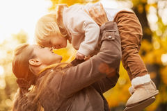 Young mother rising baby up. Young mother rising baby girl up stock photo