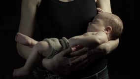 Young mother rocks to sleep a child in her arms. A dark room. Mother`s face is behind the scenes stock video