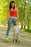 Young mother with rollers and her little son Royalty Free Stock Photos