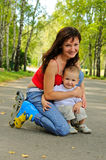 Young mother with rollers and her little son Stock Image