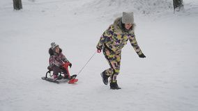 Young mother rolls her daughter on sledding in the park. Winter active family leisure. Cute woman having fun with a girl. Slow motion stock footage