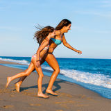 Young Mother running with daughter on beach. Royalty Free Stock Images