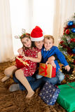 Young Mother in Santa Claus hat with son and daughter Stock Images