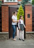 Beautiful young mother saying goodbye to her daughter leaving to school. Young mother saying goodbye to her daughter leaving to school royalty free stock photo