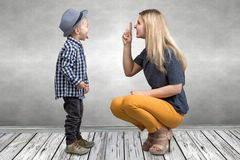 A young mother scolds her naughty little son.Boy showing tongue and teases mom. royalty free stock images