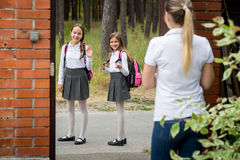 Young mother seeing of her children to school and waving to them Stock Photos