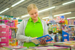 Young mother select kids books in supermarket Stock Photo