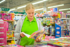 Young mother select kids books in supermarket Royalty Free Stock Images