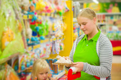 Young mother select kids toys in supermarket Stock Images