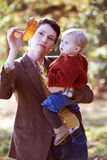 A young mother showing an autumn leaf to her baby Stock Photos