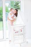 Young mother showing her daughter newborn baby. Young happy mother showing her toddler daughter a newborn baby in white round crib Stock Photos