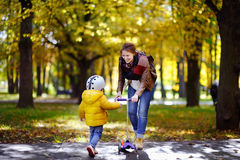Young mother showing her toddler son how to ride a scooter in a autumn park stock photography