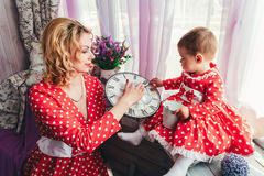 A young mother shows her one-year-old daughter a clock on a window sill in a room. Mom and daughter in red dresses Royalty Free Stock Image