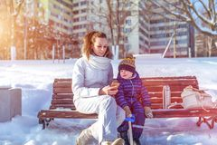 Young mother shows smartphone to child. They play sitting on a bench, in the winter in a city park on the street. Happy. Young mother shows smartphone to the stock photos