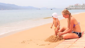 Young mother sits on mat builds sand castle against vessel stock footage