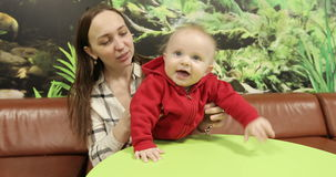 A young mother sits at a table in a cafe and plays with the baby. stock video