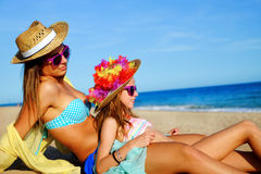 Young mother sitting with daughter on beach. Stock Photo