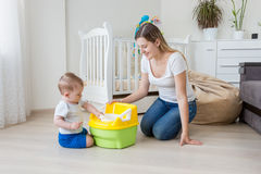 Young mother sitting on floor at living room and teaching her 10 months old baby boy how to use chamber pot royalty free stock photos