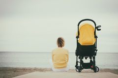 Young mother sitting next stroller by the sea Royalty Free Stock Photo