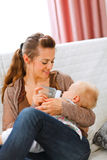 Young mother sitting on sofa and feeding her baby Stock Images